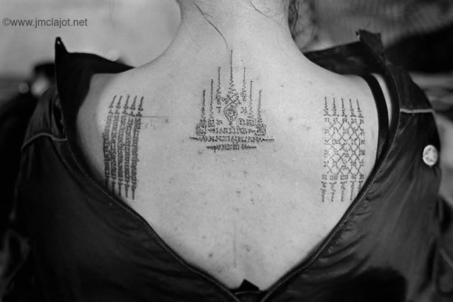 Attractive Small Thai Spiritual Tattoo On Upper Back For Girls