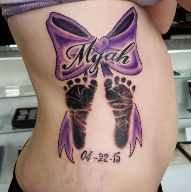 Beautiful Bow And Memorial Baby Footprints Tattoo On Side Rib