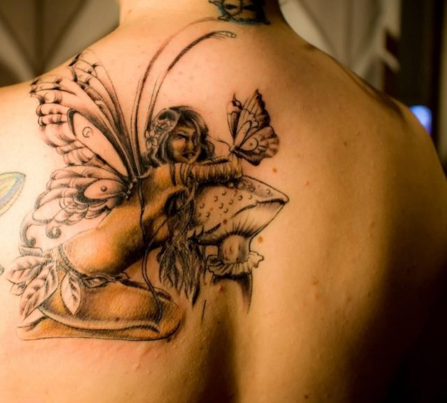 Classic Fairy On Mushroom With Butterfly Tattoo On Upper Back