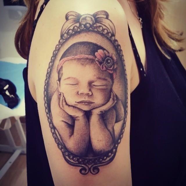 Cute Sleeping Baby Girl In Mirror Frame Tattoo On Half Sleeve
