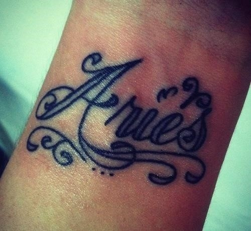 Aries lettering tattoo on wrist