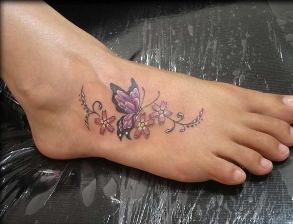 Beautiful flowers and butterfly tattoo on foot