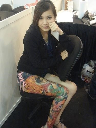 Beautiful girl with colored right sleeve leg tattoo