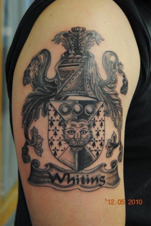 Beautiful grey ink half sleeve family crest tattoo