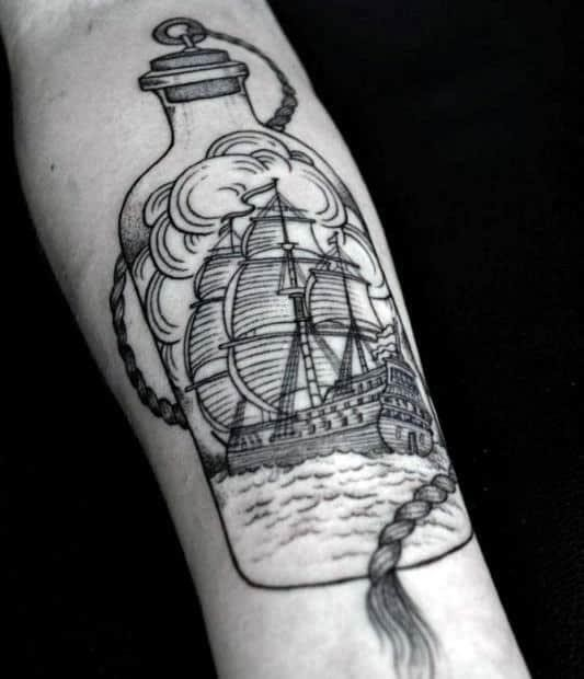 Black ink ship in a bottle inner forearm tattoo on man