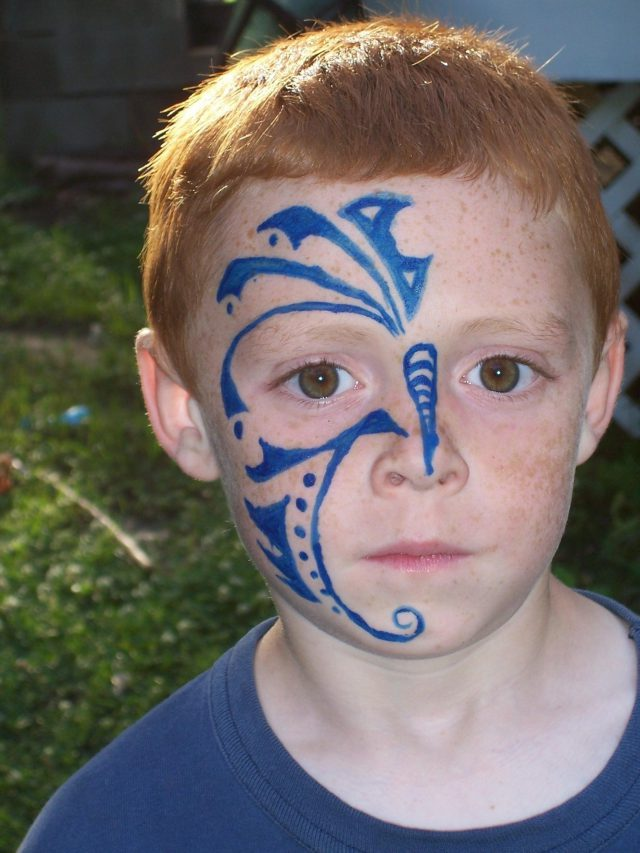 Blue ink boy face tattoo