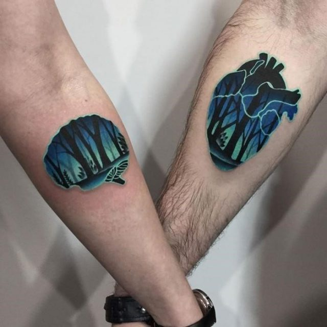 Brain and heart shapes decorated with forest scenes tattooed on the liked arms of a woman and a man matching tattoos for couples in love