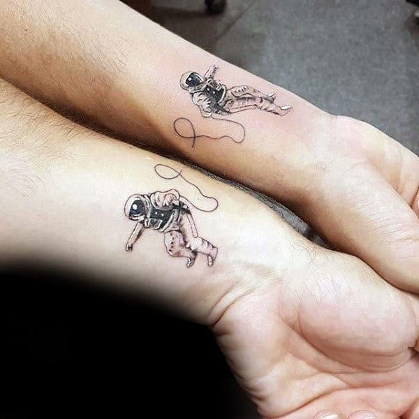 Cool small simple brothers astronaut tattoos on wrists