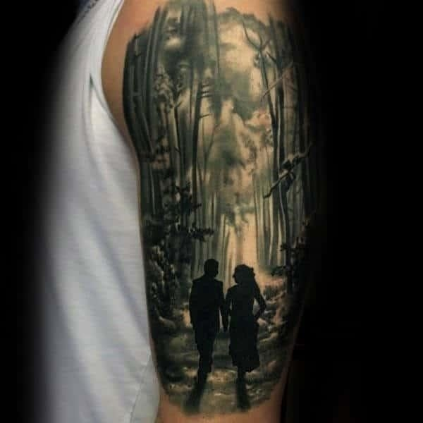 Couple walking through forest mens upper arm tattoo