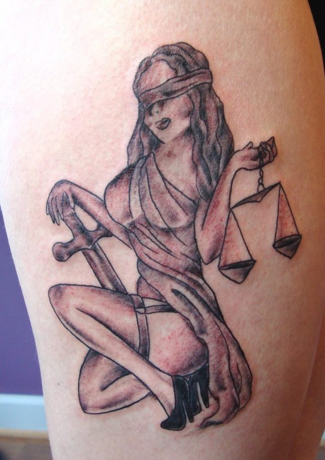 Girl with cross and balance justice tattoo