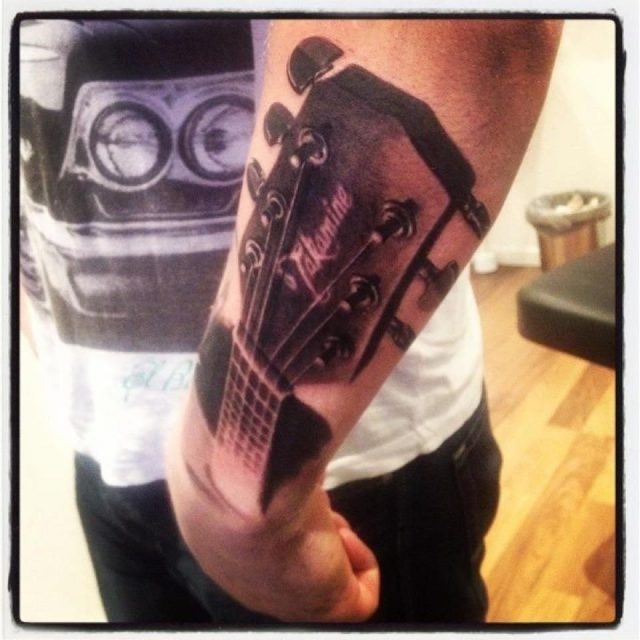 Grey ink guitar tattoo on left arm