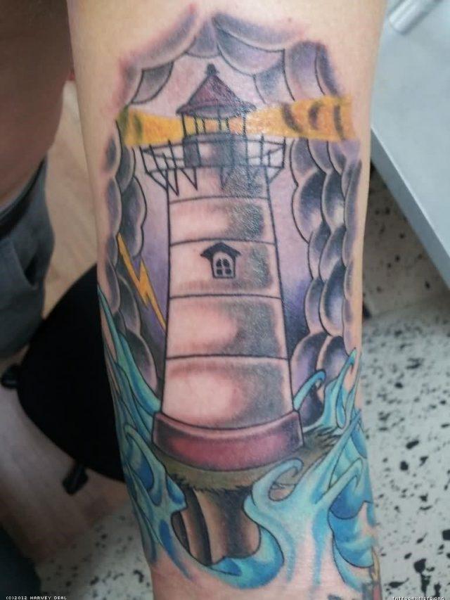 Grey ink lighthouse tattoo on leg sleeve