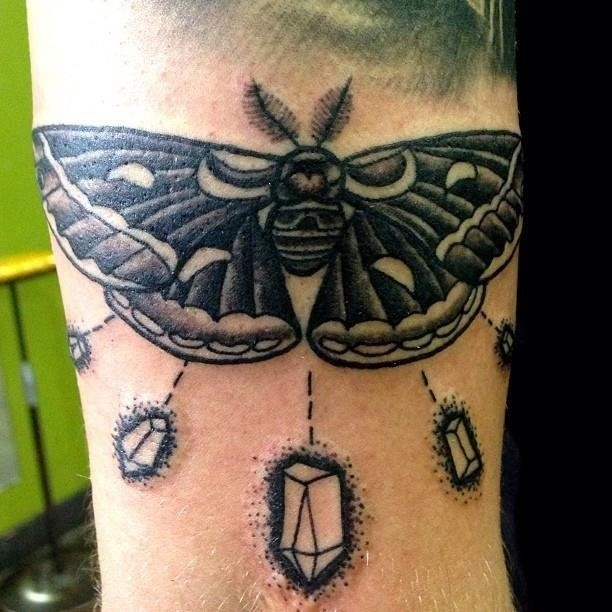 Grey ink moth tattoo on right triceps