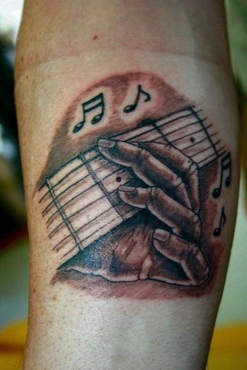 Guitar music notes tattoo on arm