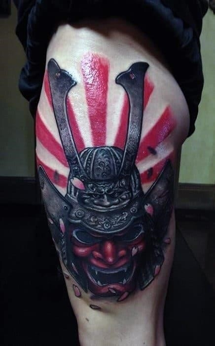 Guys thigh tattoo of samurai mask with rising sun flag background