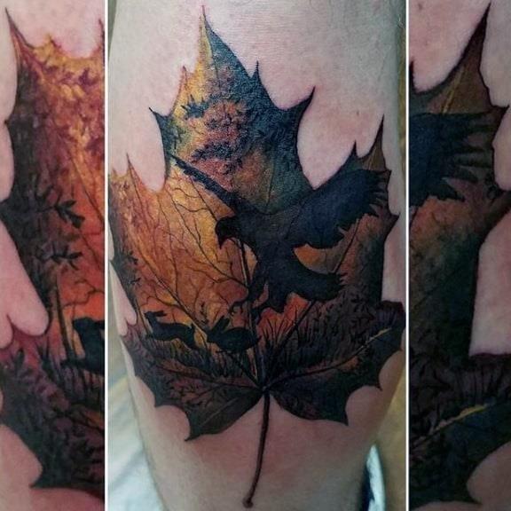 Hawk picking up rabbit maple leaf mens leg tattoo