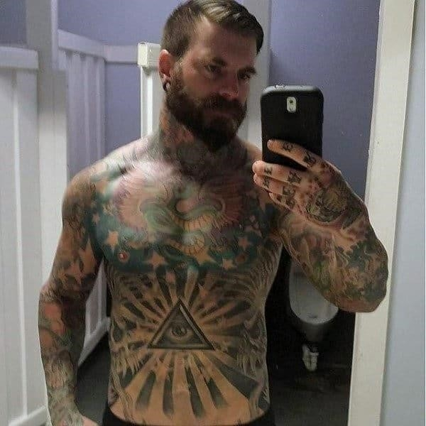 Illuminati themed male stomach tattoo with all seeing eye and sun rays