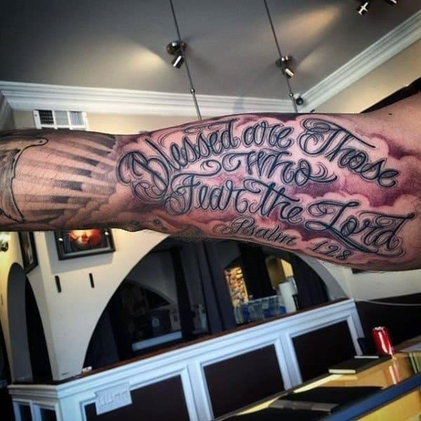 Inner biceps religious tattoo for men