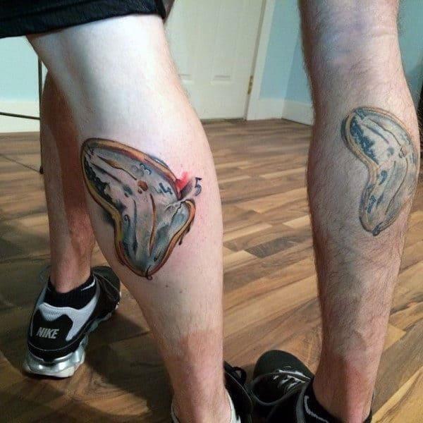 Leg calf melting clock tattoo on male