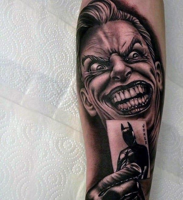 Mens joker holding playing card of batman arm tattoos