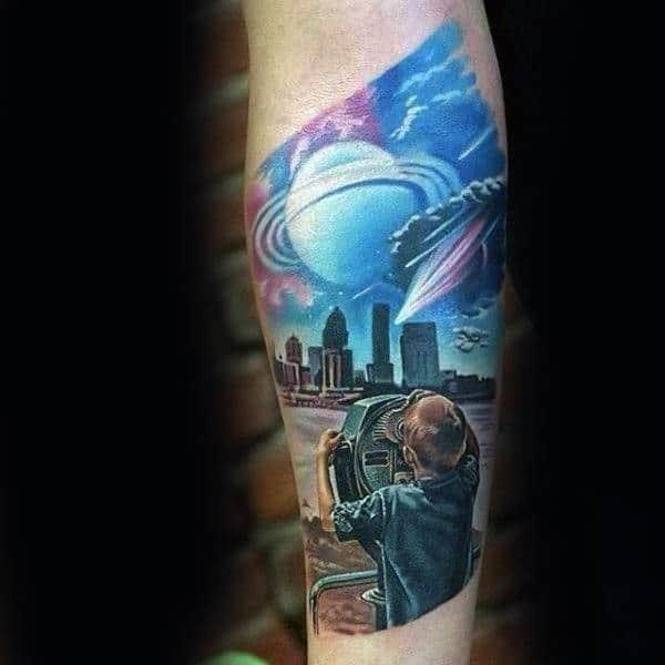 Young male looking through telescope mens tattoo tattoo with city skyline background